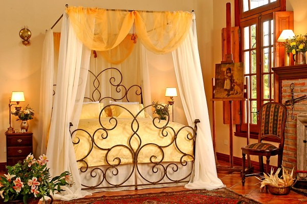 Delazious wrought iron canopy bed with yellow and white drapery and bedding