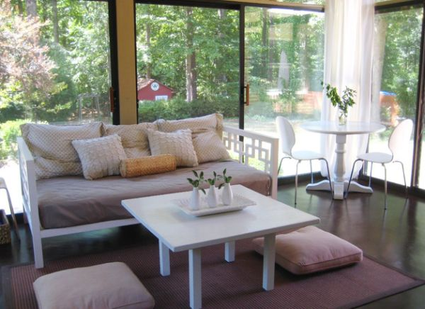 Elegant porch with floor pillows that match the hue of the sofa and the rug