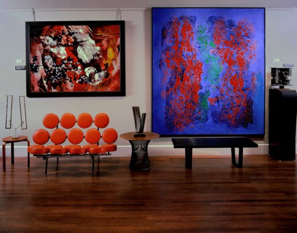 Marshmallow Sofa in bright orange flanked by interesting art work Inspirational George Nelson Designs: From Iconic Clocks To Ingenious Sofas!