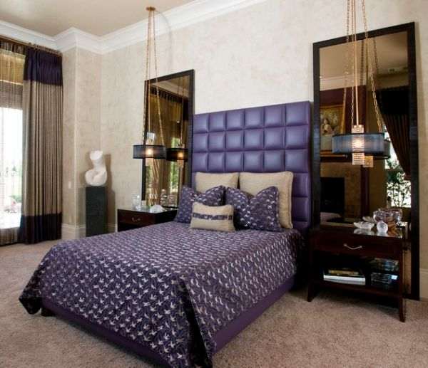 Purple headboard and brilliant chandeliers shape an opulent bedroom
