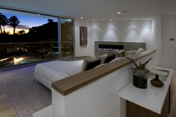 Recessed lighting and patio fireplace accentuate the beauty of the bedroom