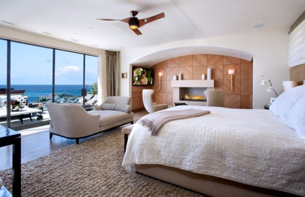 Spacious bedroom with a modern seating nook next to the fireplace