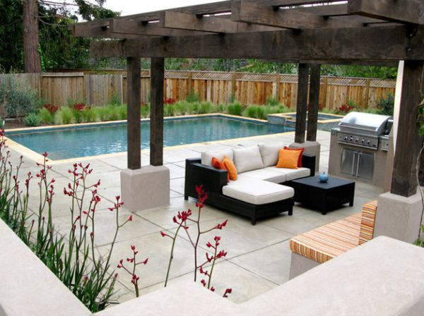 White cushions and deck space offer a lovely contrast to the dark wood of the pergola
