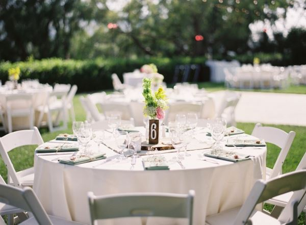 White tables and chairs on a green lawn