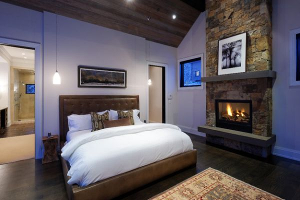 View in gallery Wooden ceiling and stone fireplace give the bedroom a  luxury cabin appeal