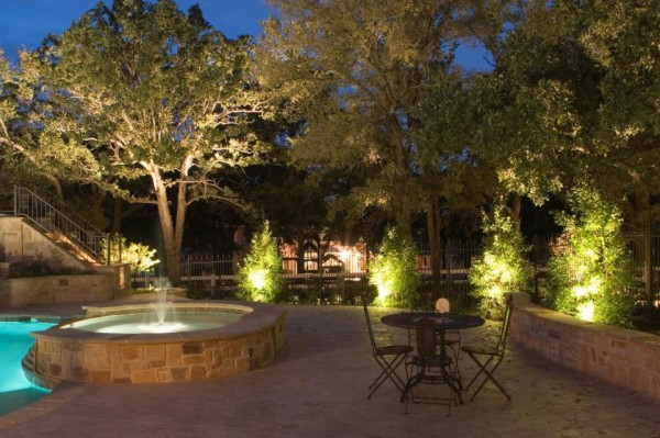 small fountain and tree lighting in garden sitting area