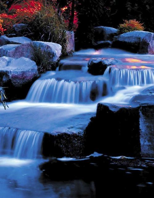dramatic lighting of water feature in garden