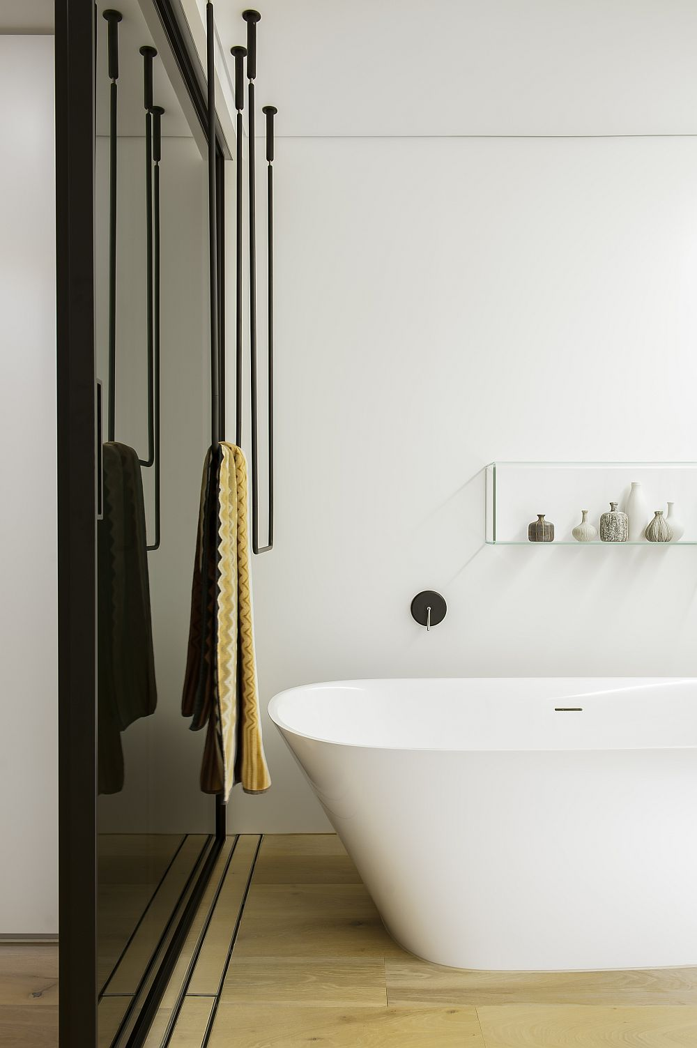 Dark grey sliding glass doors complement white corain walls
