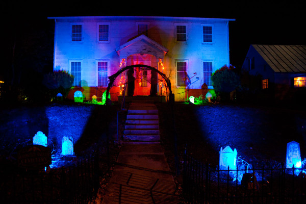 Haunted house with dark path through Halloween graveyard