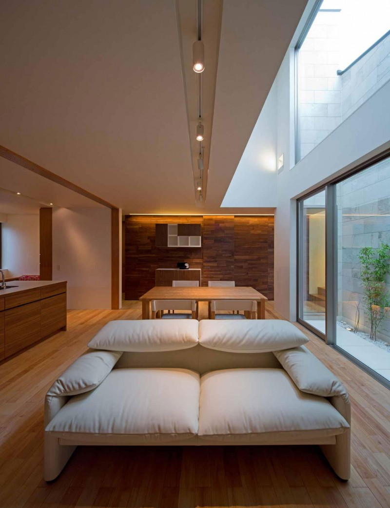 Minimalist japanese residence blends privacy with an airy for Modern living room high ceiling