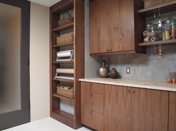 Open shelving with exposed brackets reinforces the industrial look of this laundry room
