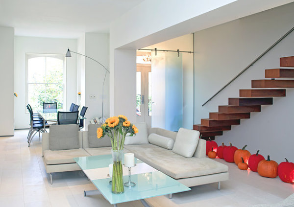 Pumpkins line the floor of a modern home