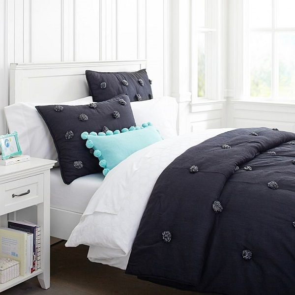 Solid black comforter with pom poms