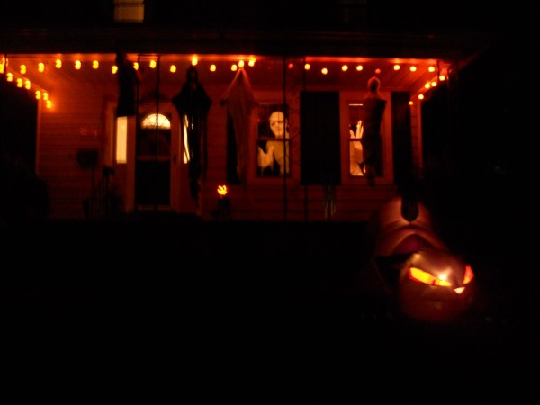 dark orange porch with bright figures in windows