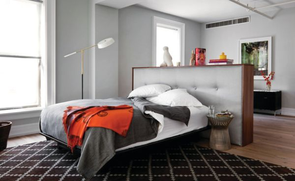 Bachelor pad uses a tufted headboard to demarcate the bedroom area