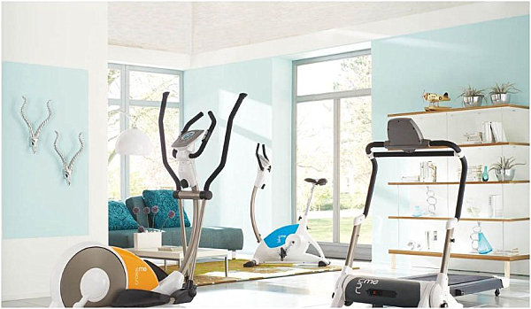 Blue and white home gym with plush seating area
