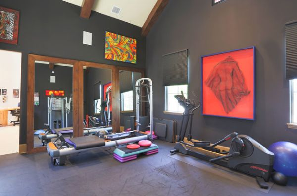 large glass windows visually connect the home gym with the canopy outside view in gallery bright artwork on the walls adds color to the dark room - Home Gym Design Ideas