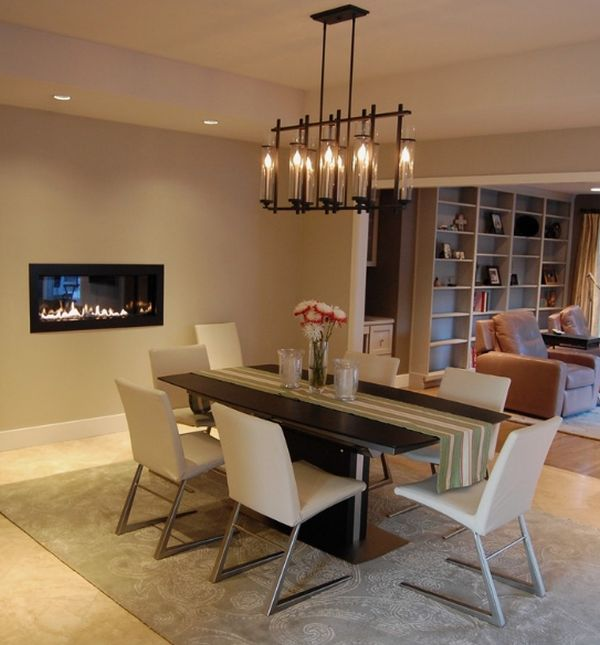 Chandelier above the dining table complements the fireplace stylishly