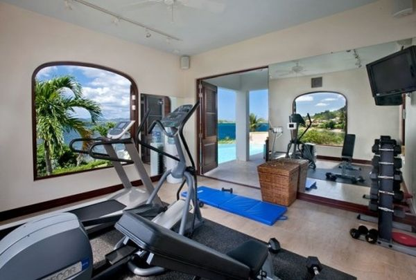 Large glass windows visually connect the home gym with the canopy outside