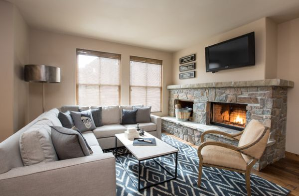 Patterned rug and a stone fireplace give this bachelor pad a cozy and classic vibe