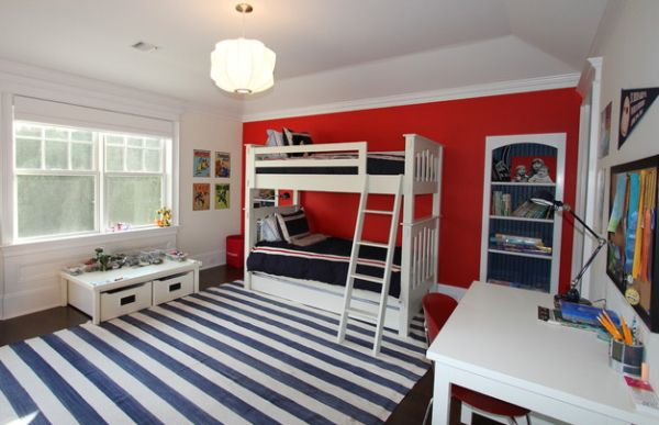 Red accent wall makes an interesting addition to this kids' bedroom