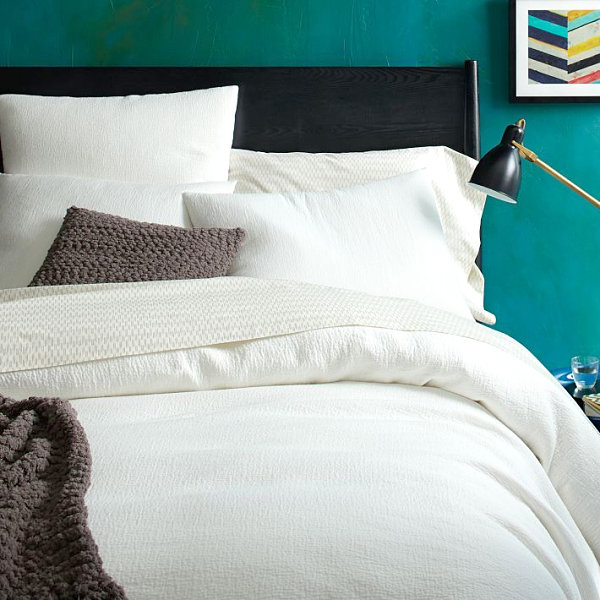 Teal bedroom with white duvet