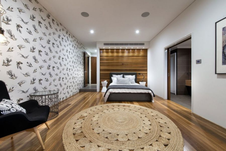 Warm wood accents and interesting wallpaper in the bedroom