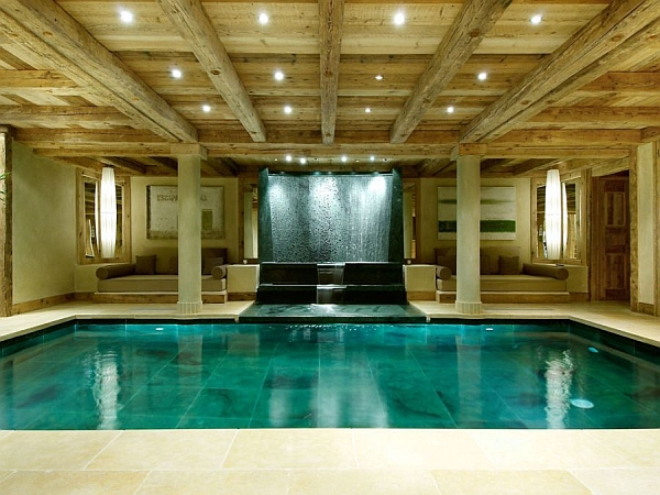 Captivating indoor pool features a waterfall backdrop