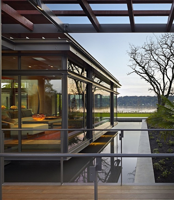 Glass house with lake views seems to levitate above the cool reflecting pool