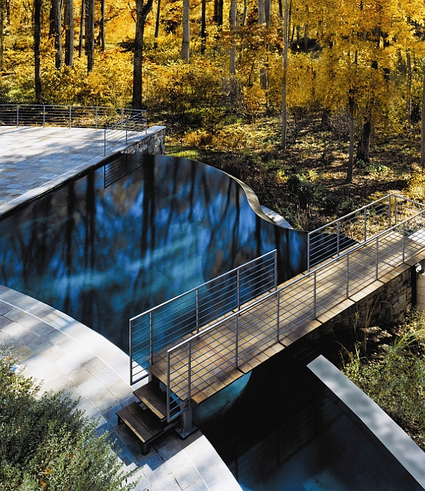 Stunning free-form pool with negative edge and a wooden bridge surrounded by lovely canopy