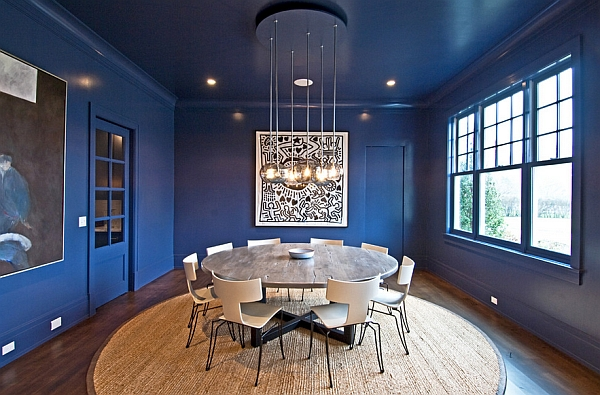 Dramatic dining room in blue with a round table and Anziano chairs