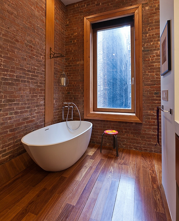 Exposed brick wall and warm wooden floor complement the modern bathtub elegantly