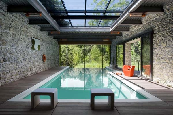 Indoor pool with stone walls and glass roof