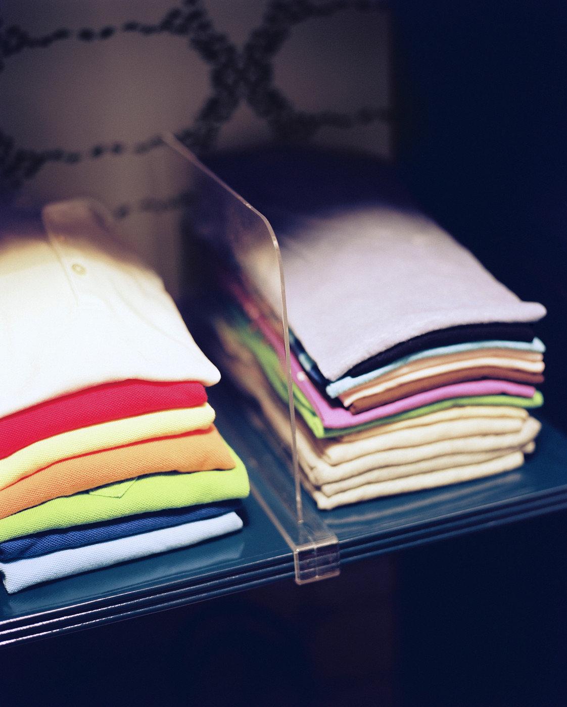Neatly folded shirts in an organized closet