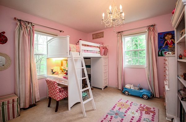 Cute girls' bedroom in pink with a loft bed and storage space along with a work table