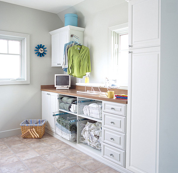 Open shelving with pullout drawers in a crisp laundry room