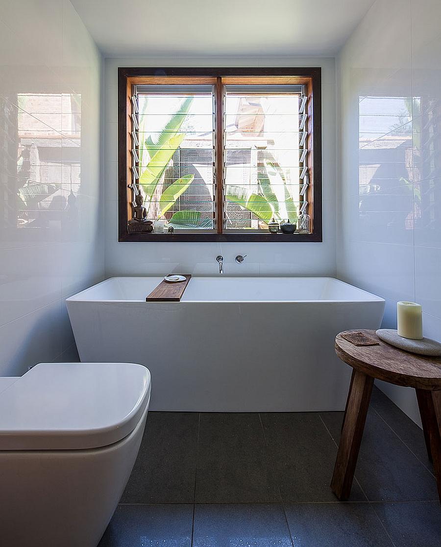 Bathtub in white next to the window