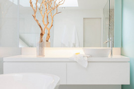 Branches add a dramatic touch to a crisp bathroom