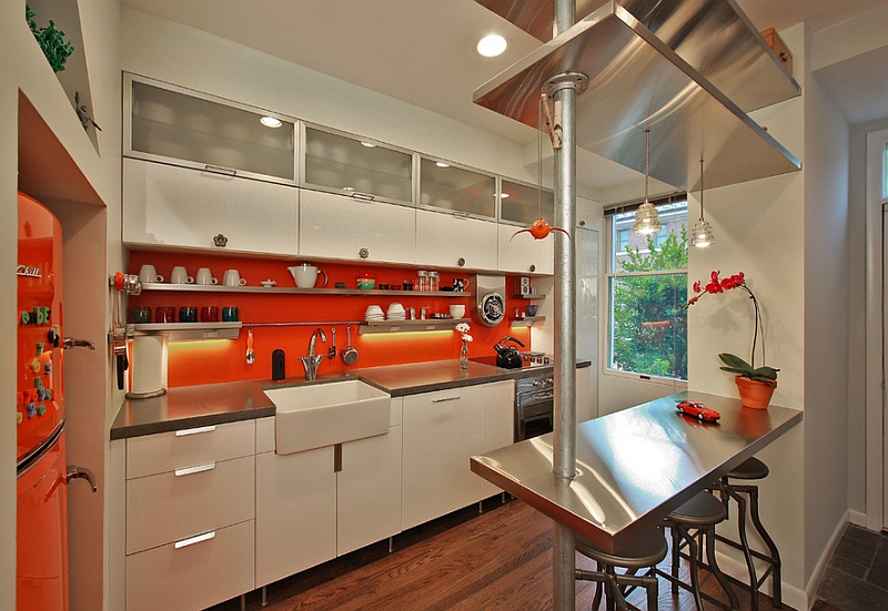 Bright orange backsplash in the compact kitchen