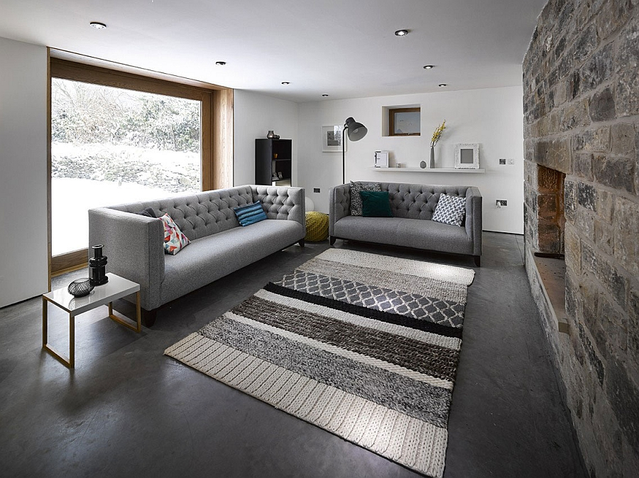 Comfy grey couch in the living space Gorgeous 16th Century Barn In Yorkshire Gets A Restrained Modern Revamp