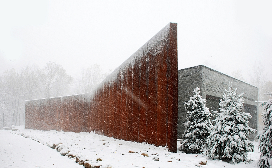 Curved Corten wall protects the house from the elements