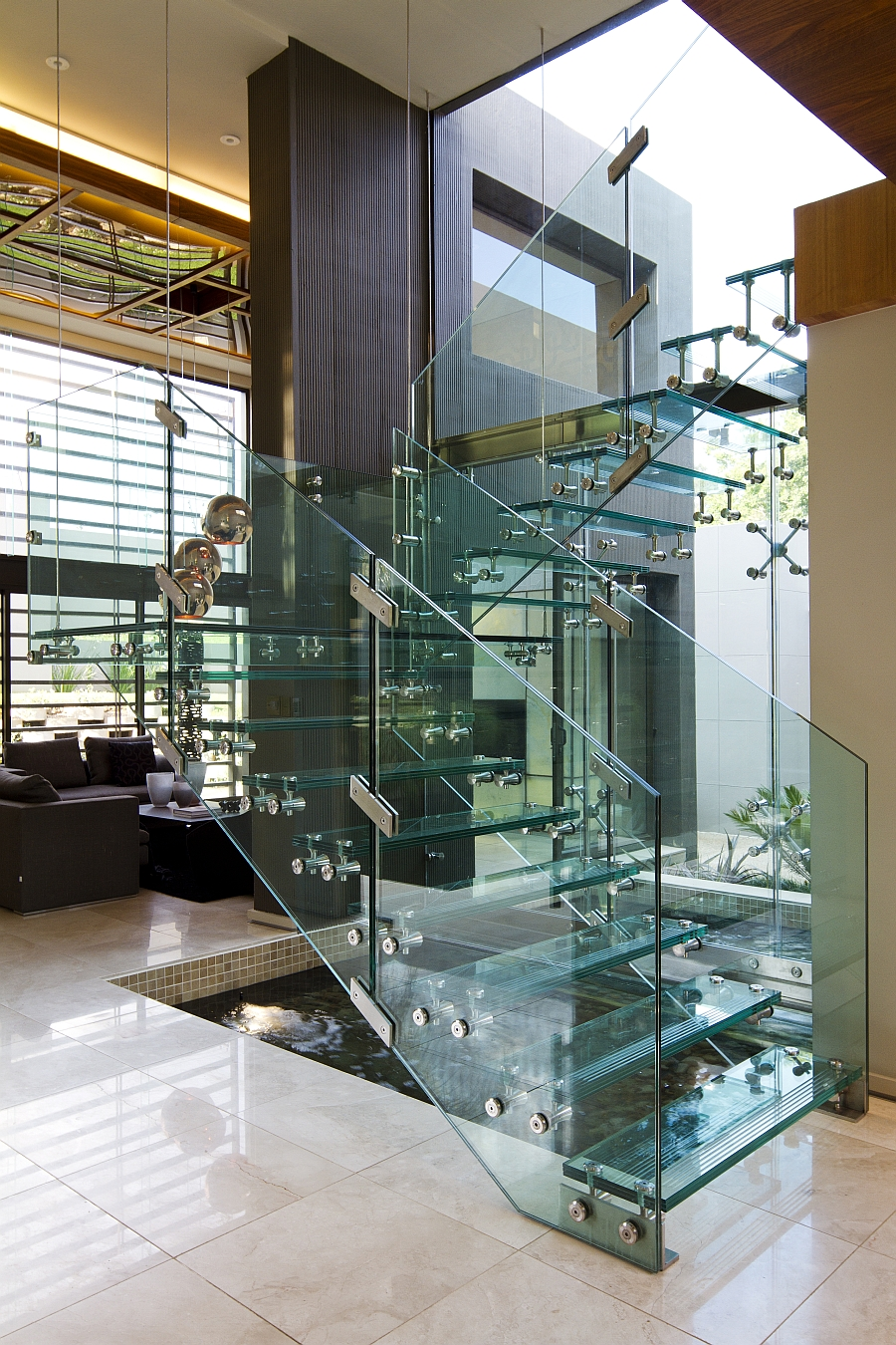 Glass staircase and indoor water feature at House Sed
