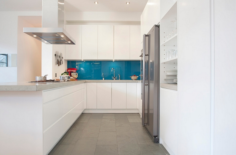 Grey concrete worktops combined with peacock blue splashback
