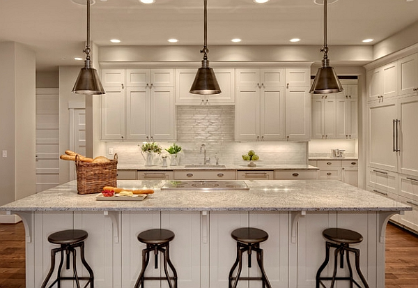 Metal pendant lights above the kitchen counter stand out thanks to the neutral backdrop