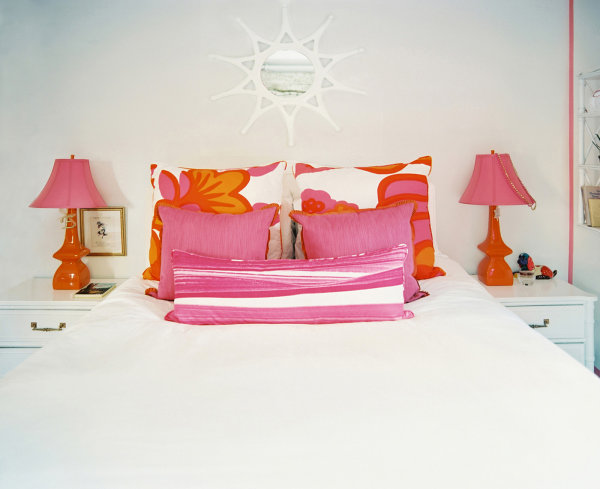 Orange and pink wake up this all-white master bedroom