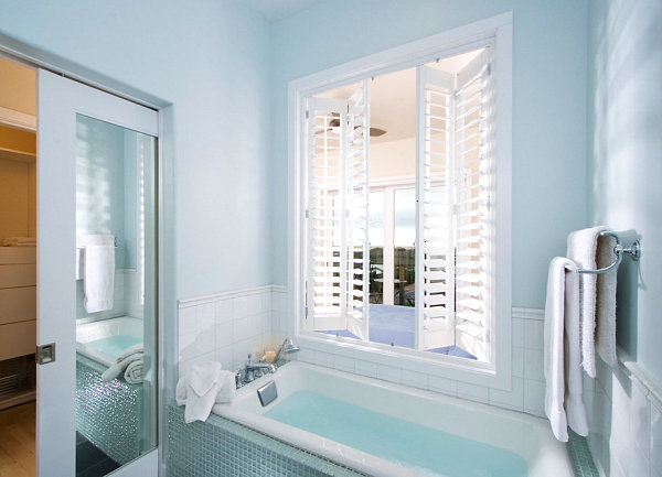 Sliding door within a powder blue bathroom