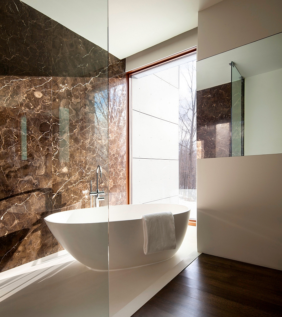 Standalone bathtub next to the glass window