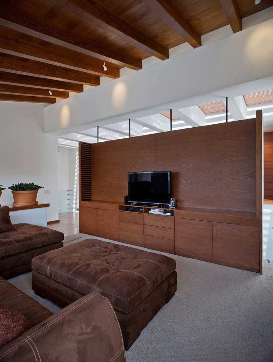 Wooden ceiling and large entertainment wall add warmth to the space