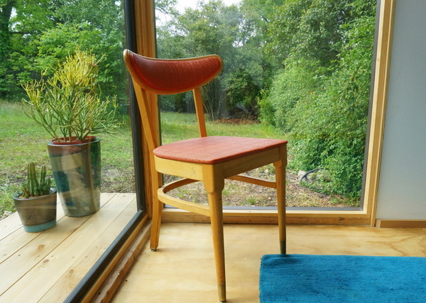 A Mid-century chair sits in the window