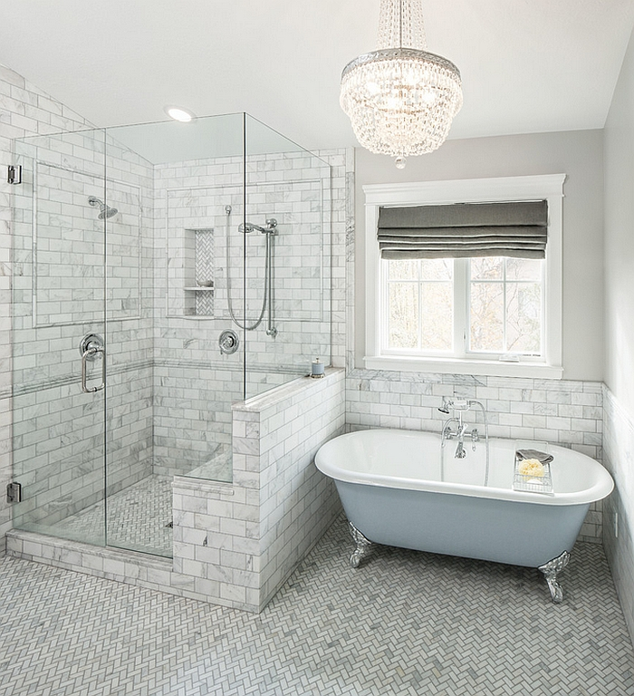 Bathroom in soft grey and blue with herringbone floors and a painted bathtub